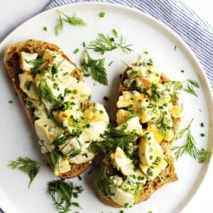 egg salad on sourdough slices on a white plate