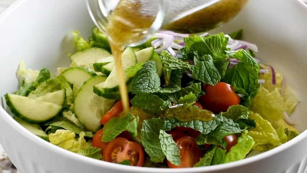 pouring dressing over fattoush salad