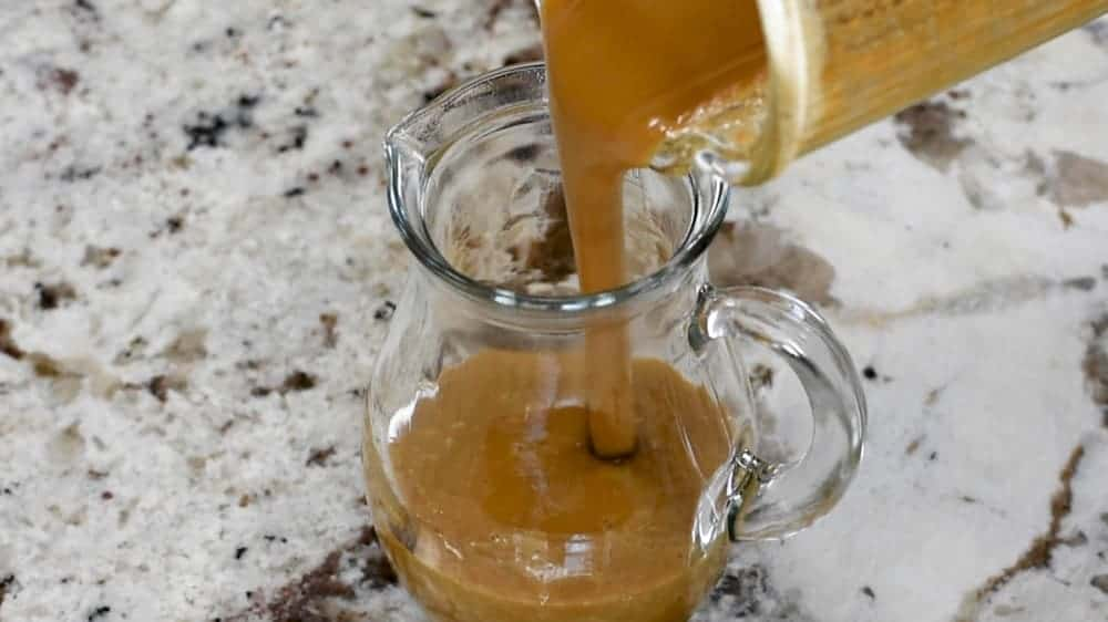 transferring balsamic vinaigrette to serving pitcher
