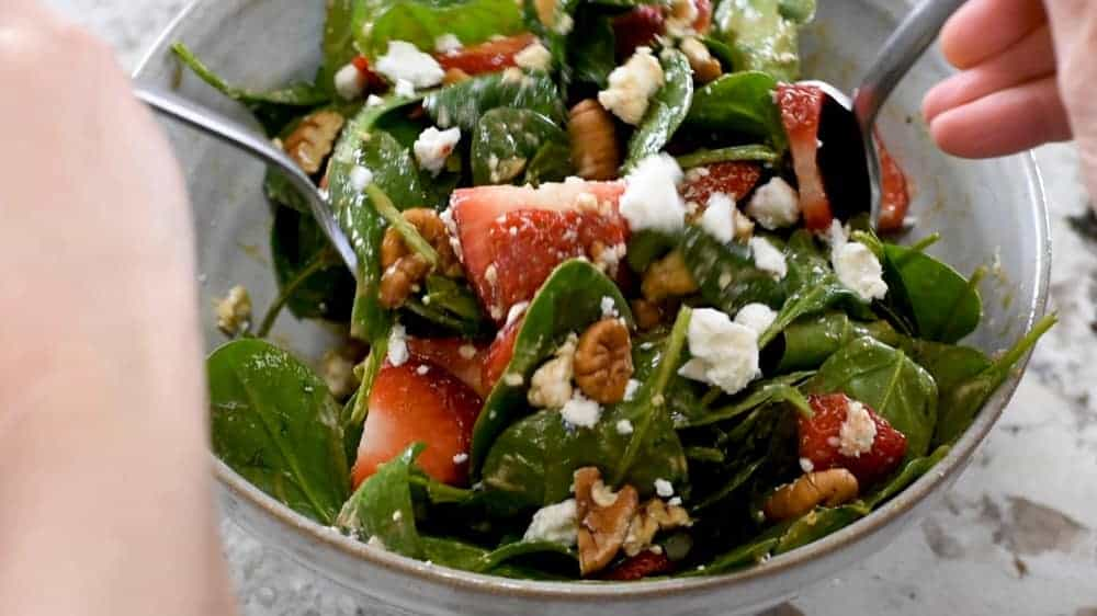 tossing spinach salad ingredients with balsamic dressing