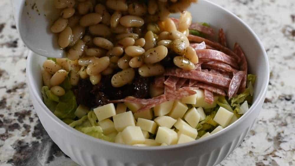 adding marinated beans to Italian salad