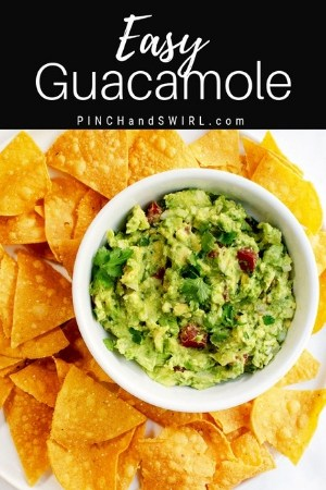guacamole served in a white bowl with tortilla chips surrounding it