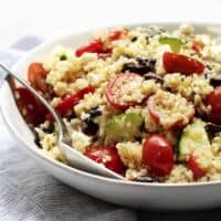 Greek quinoa salad served in a shallow white bowl