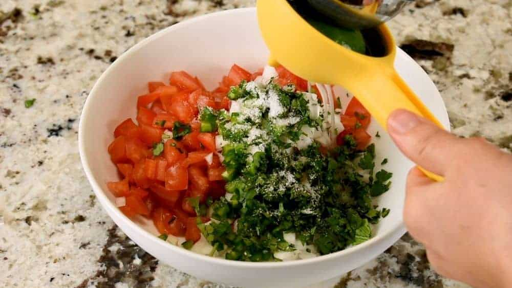 squeezing lime over pico de gallo ingredients