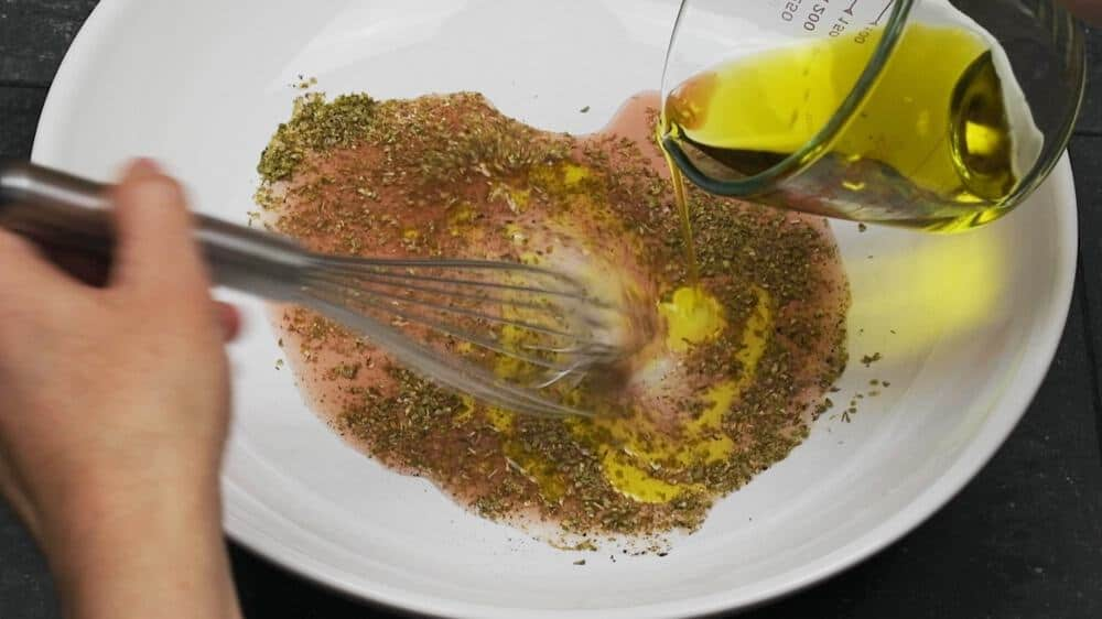 whisking greek quinoa salad dressing in the bottom of a wide white bowl