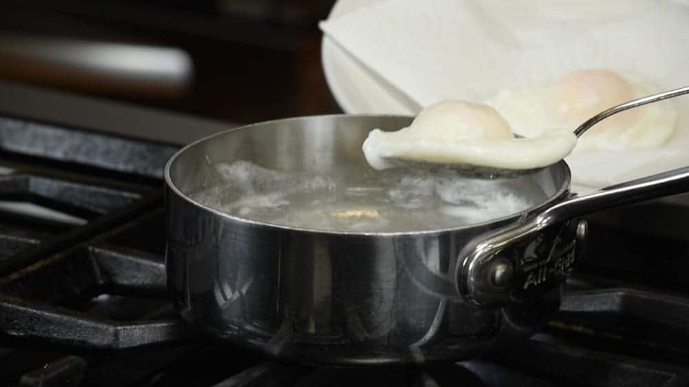 transferring a poached egg to a paper towel