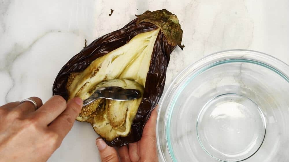 scooping flesh from a roasted eggplant