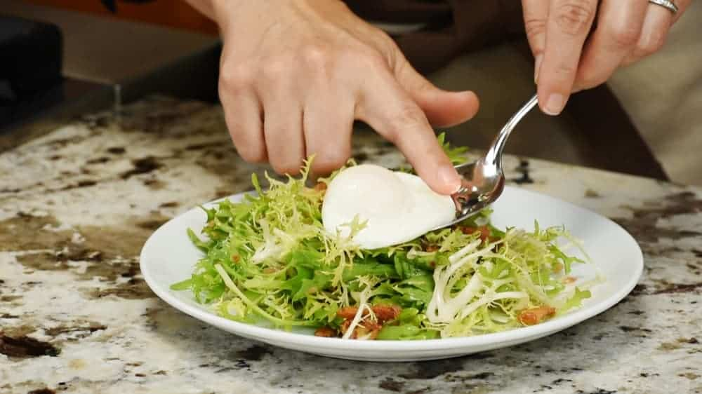 topping Salad Lyonnaise with poached egg