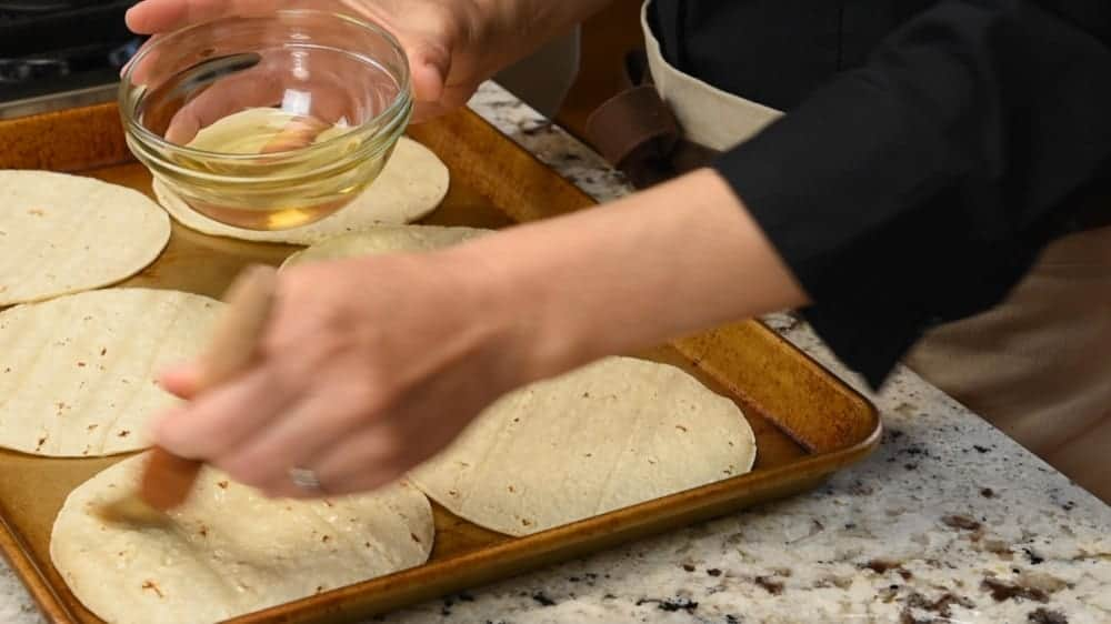 brushing corn tortillas with oil