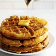 pouring syrup over a stack of Belgian Waffles