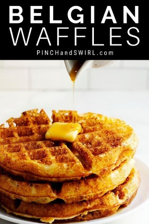 pouring syrup over stacked belgian waffles
