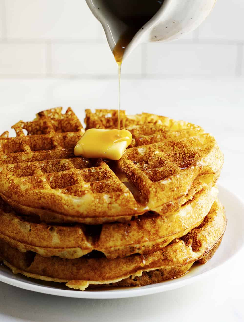 pouring syrup over belgian waffles