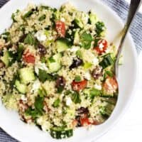 Quinoa Tabbouleh Salad served in a white bowl with stainless spoon
