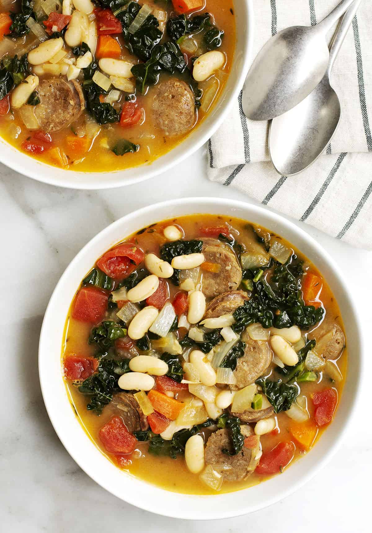 white bean sausage and kale soup served in white bowls