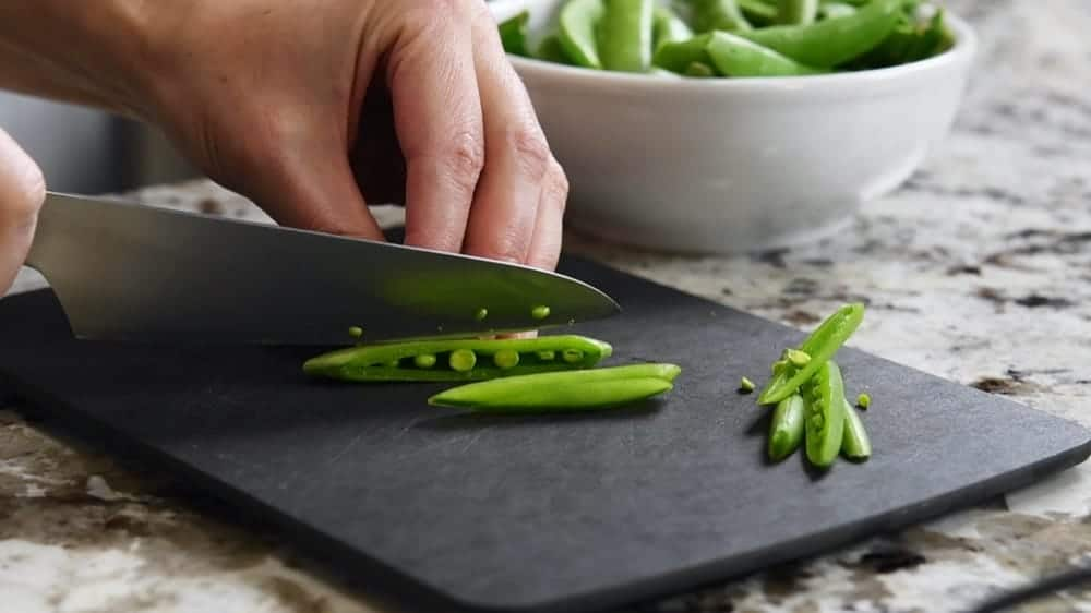 hand slicing Sugar Snap Peas with a sharp knife