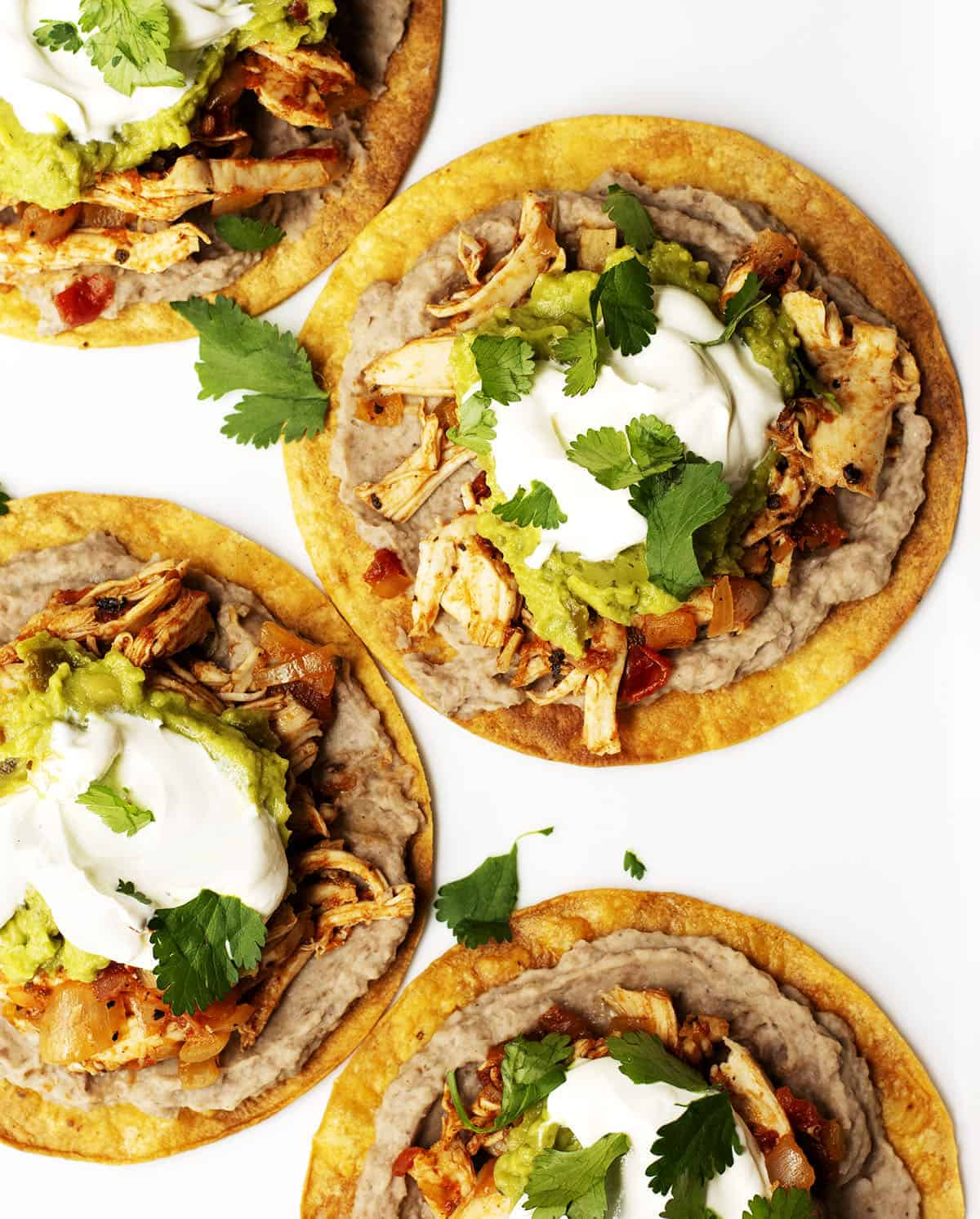 chicken tostadas served on a white platter with lime wedges