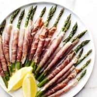 Prosciutto Wrapped Asparagus arranged on a round platter with lemon wedges