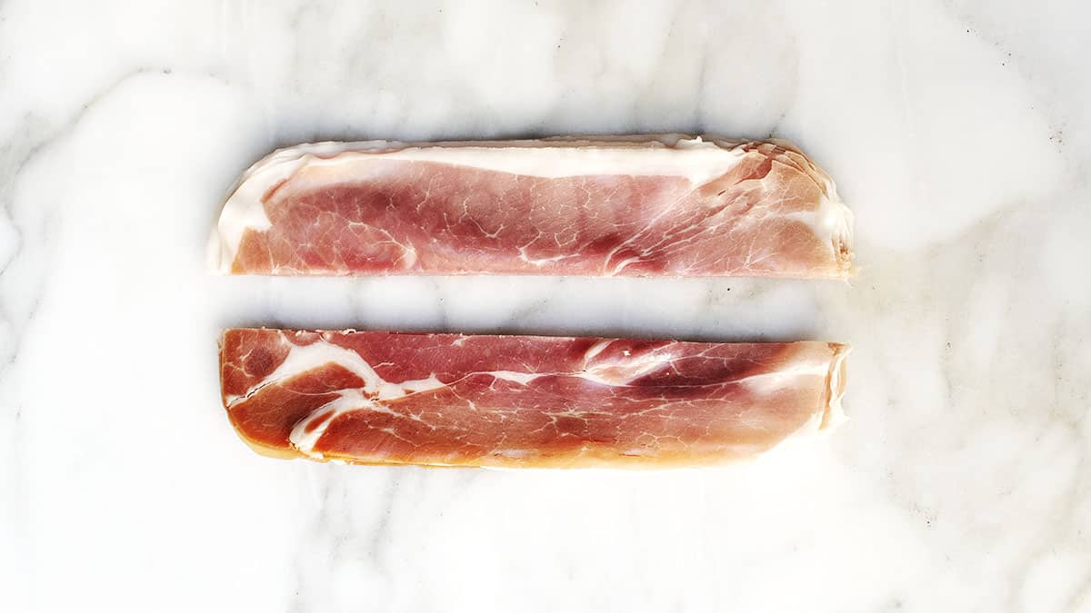 paper thin slices of prosciutto stacked and cut in half lengthwise