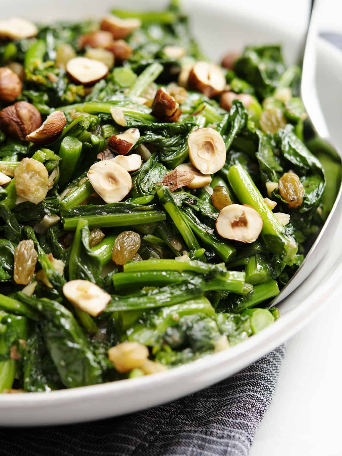 Rapini (Broccoli Rabe) with Raisins and Hazelnuts served in a white bowl