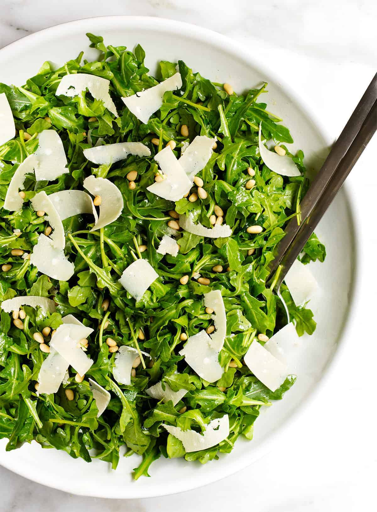 arugula salad in a white bowl photographed from above
