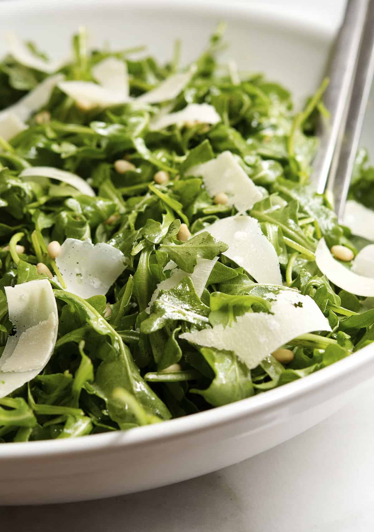 arugula salad in a white bowl