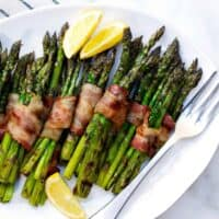 Grilled Bacon Wrapped Asparagus on a white platter
