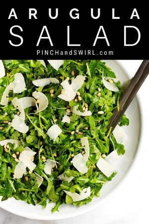 arugula salad in a shallow white serving bowl
