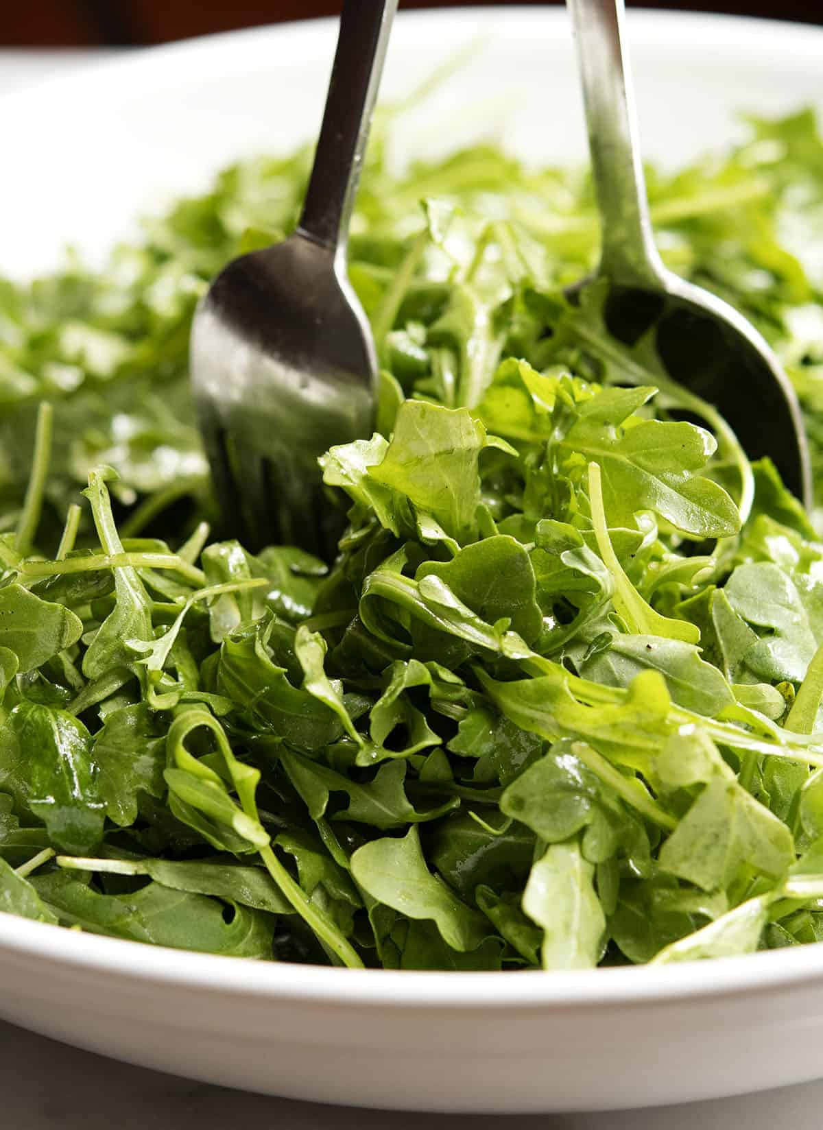 tossing arugula with dressing