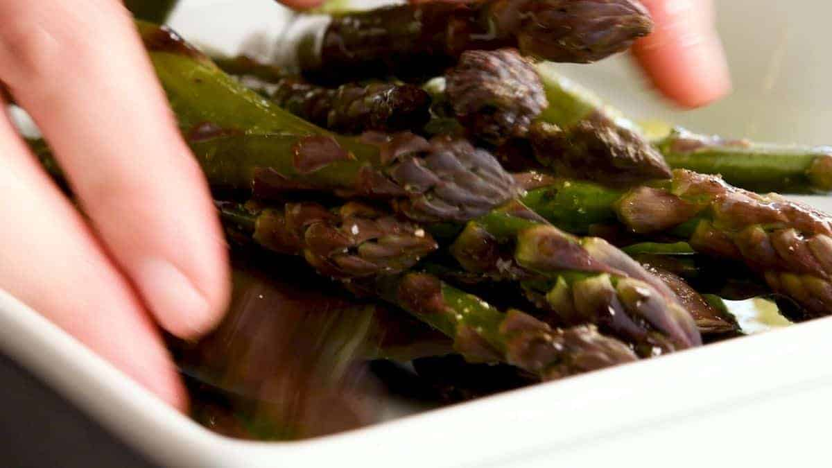 tossing asparagus in olive oil salt and pepper