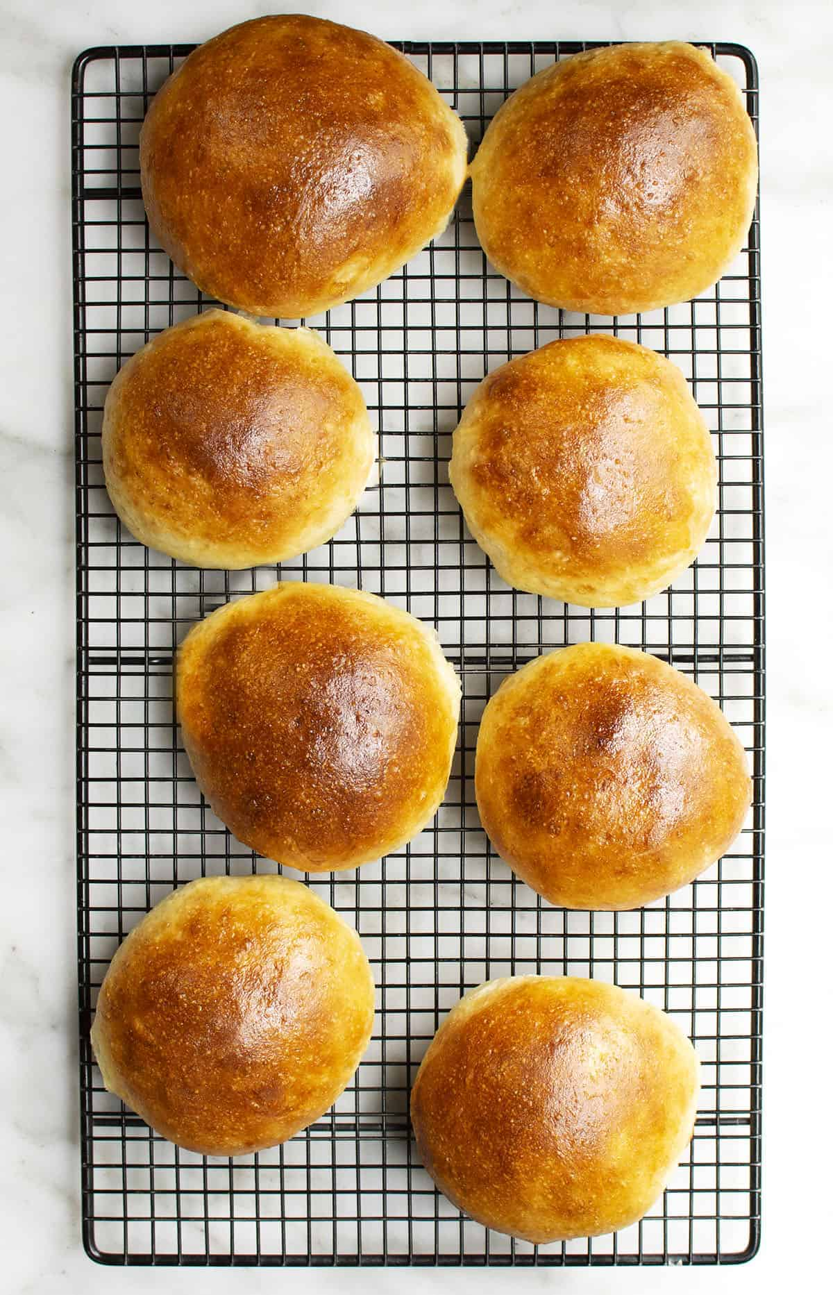 brioche buns on black wire cooling rack