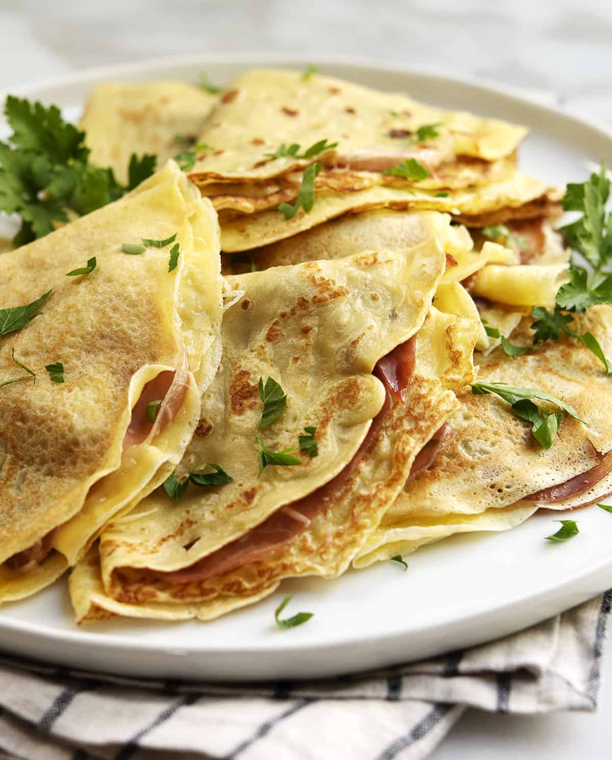 savory crepes layered on a white plate