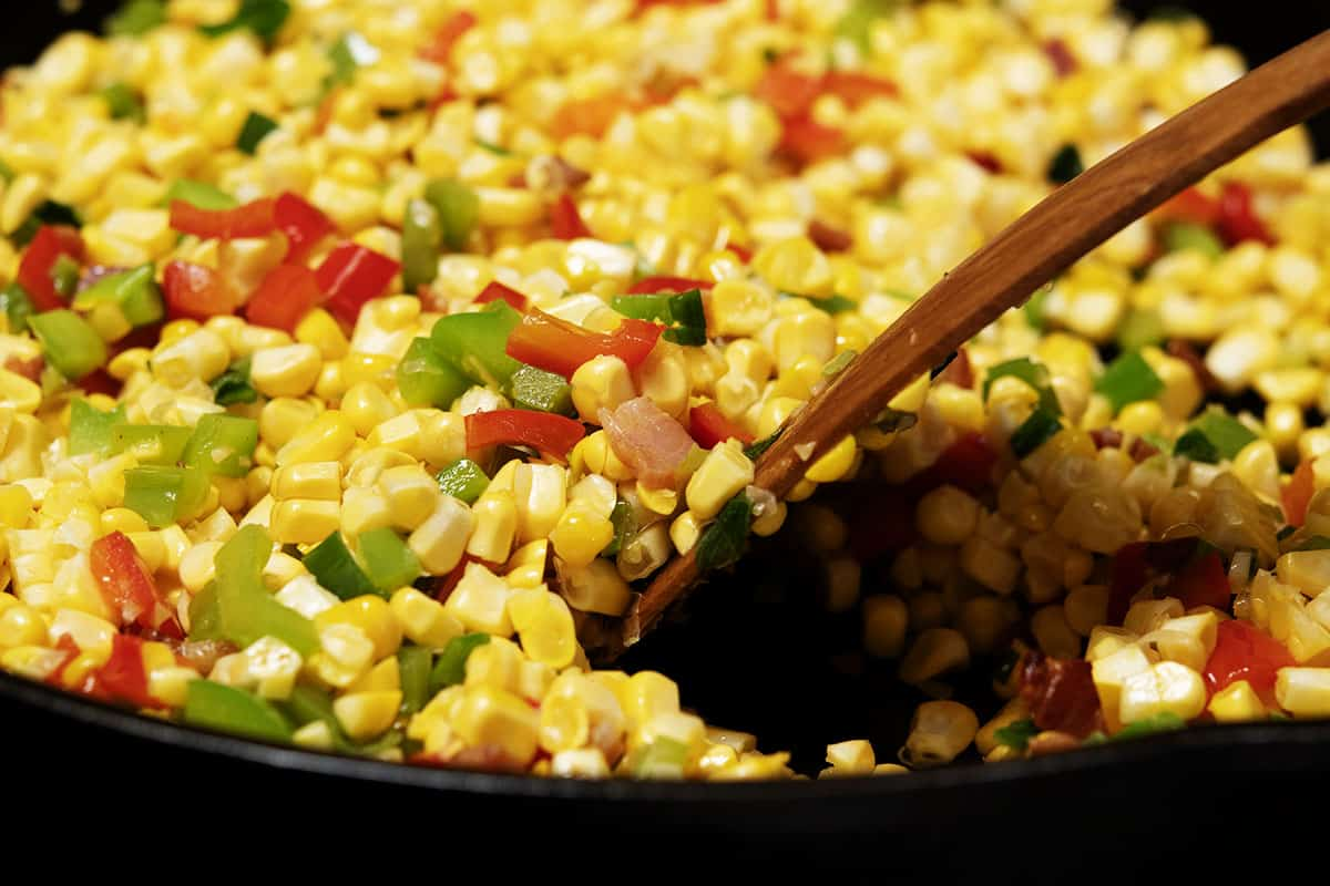 stirring corn kernels into bell pepper mixture