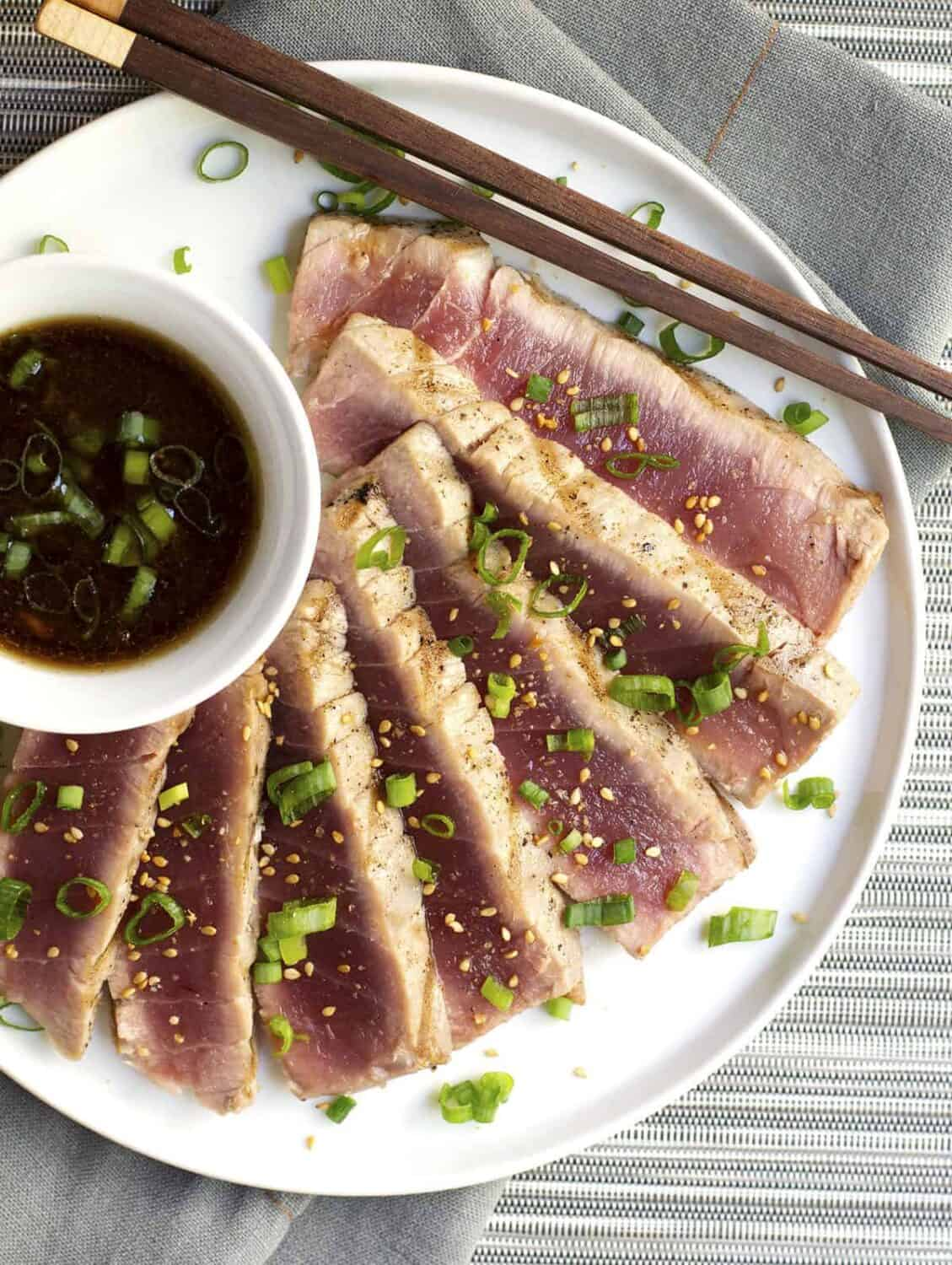 Grilled Tuna Steaks served on a white plate photographed from above