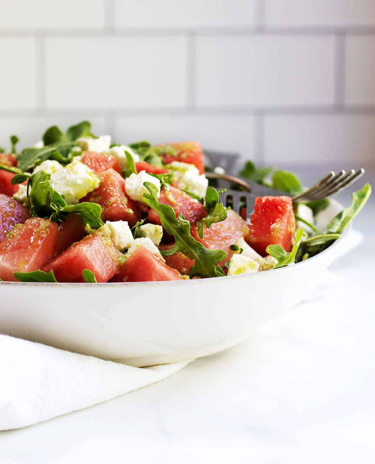 watermelon and arugula salad with feta served in a white ceramic bowl
