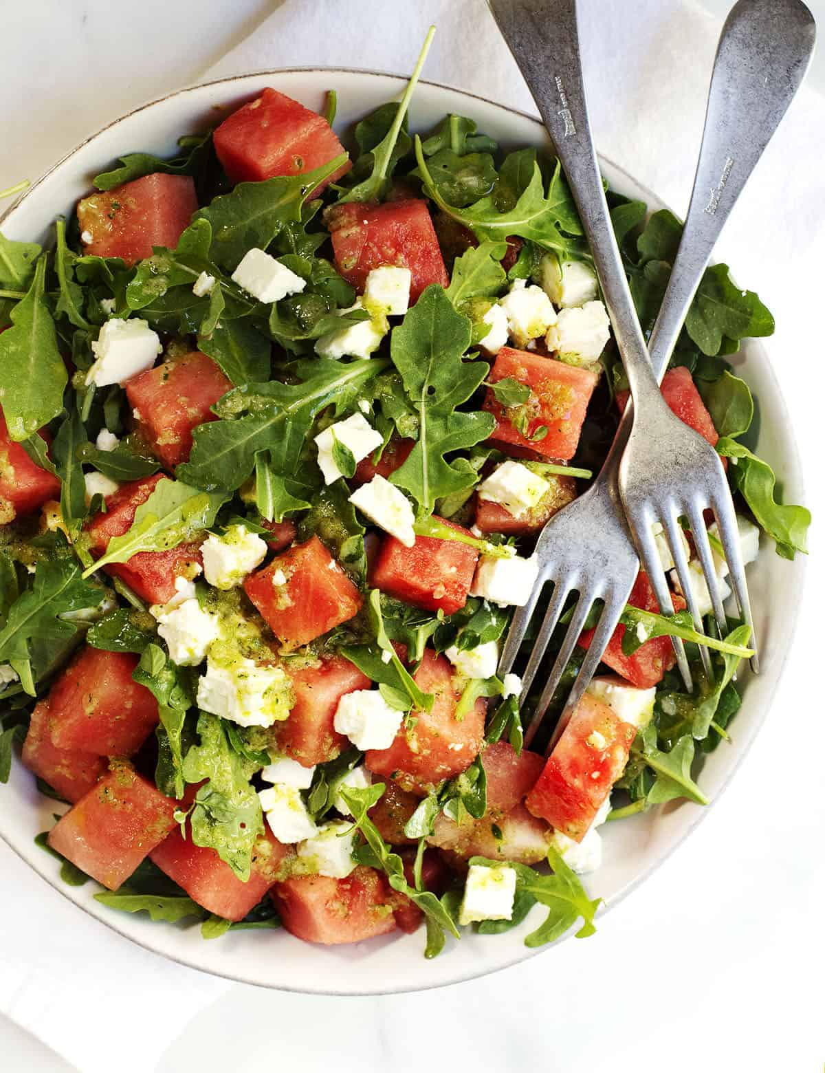 Watermelon and Arugula Salad with Feta Cheese in a ceramic bowl photographed from above
