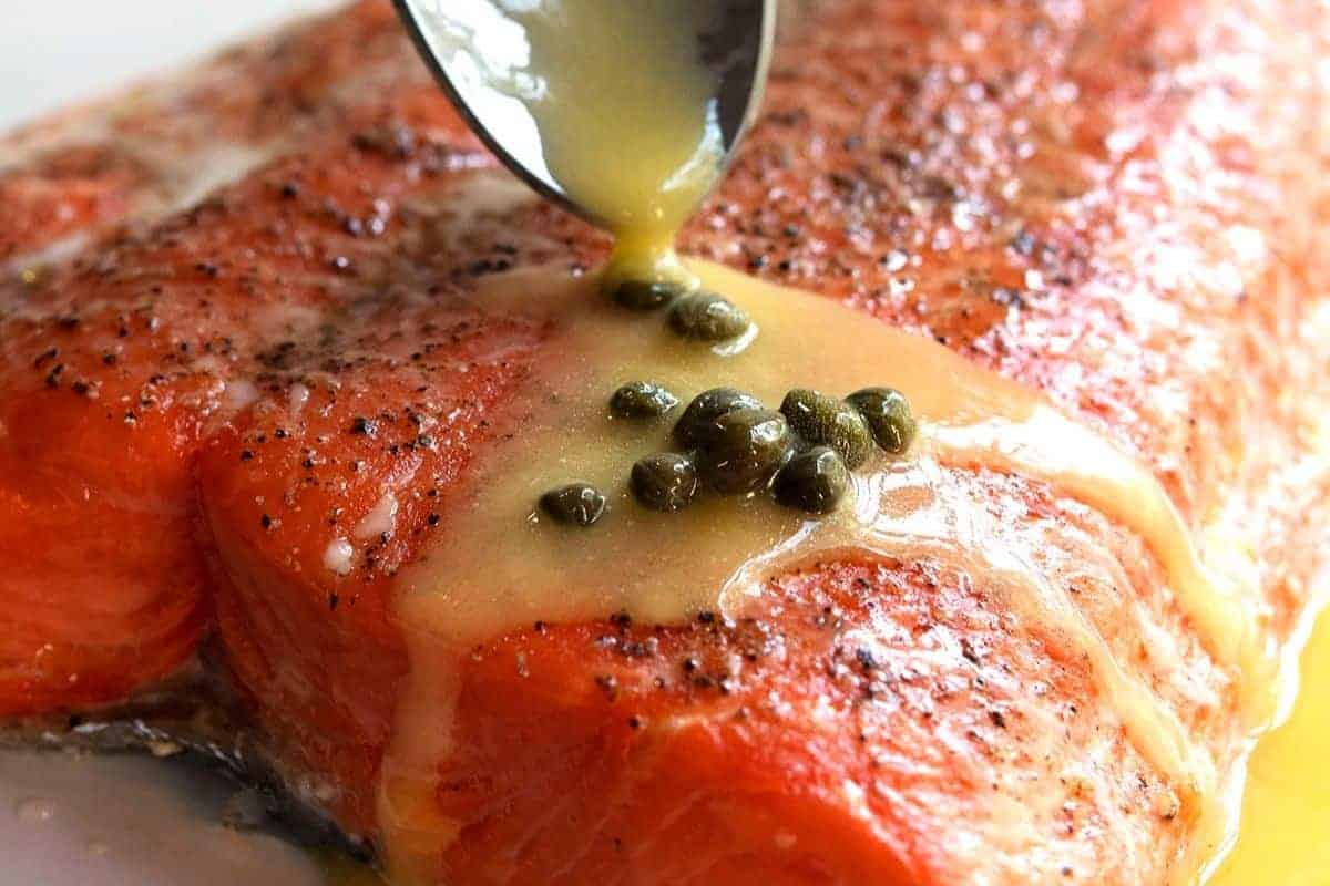 spooning lemon butter sauce with capers over salmon