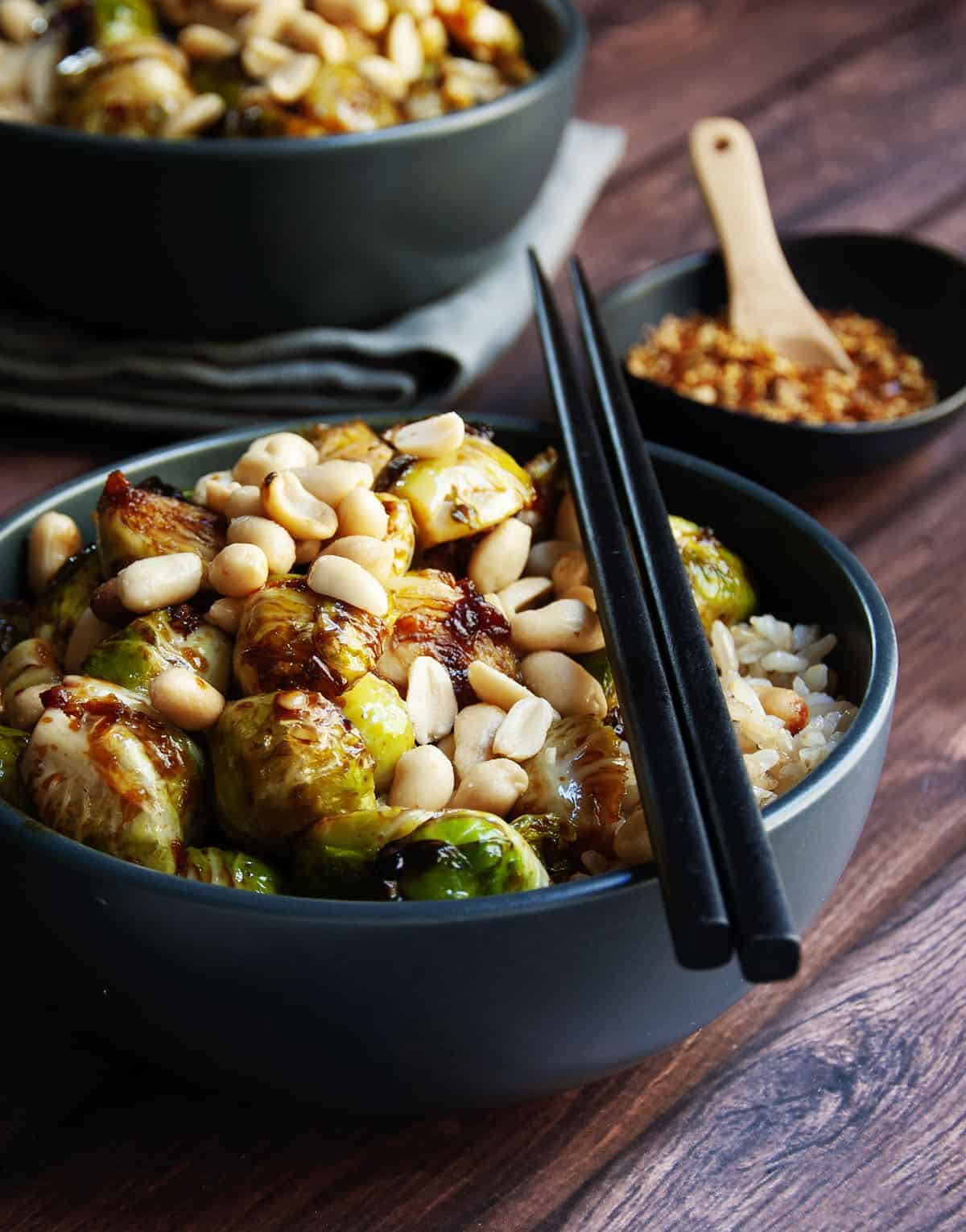 Kung Pao Brussels Sprouts served in a black bowl with chopsticks