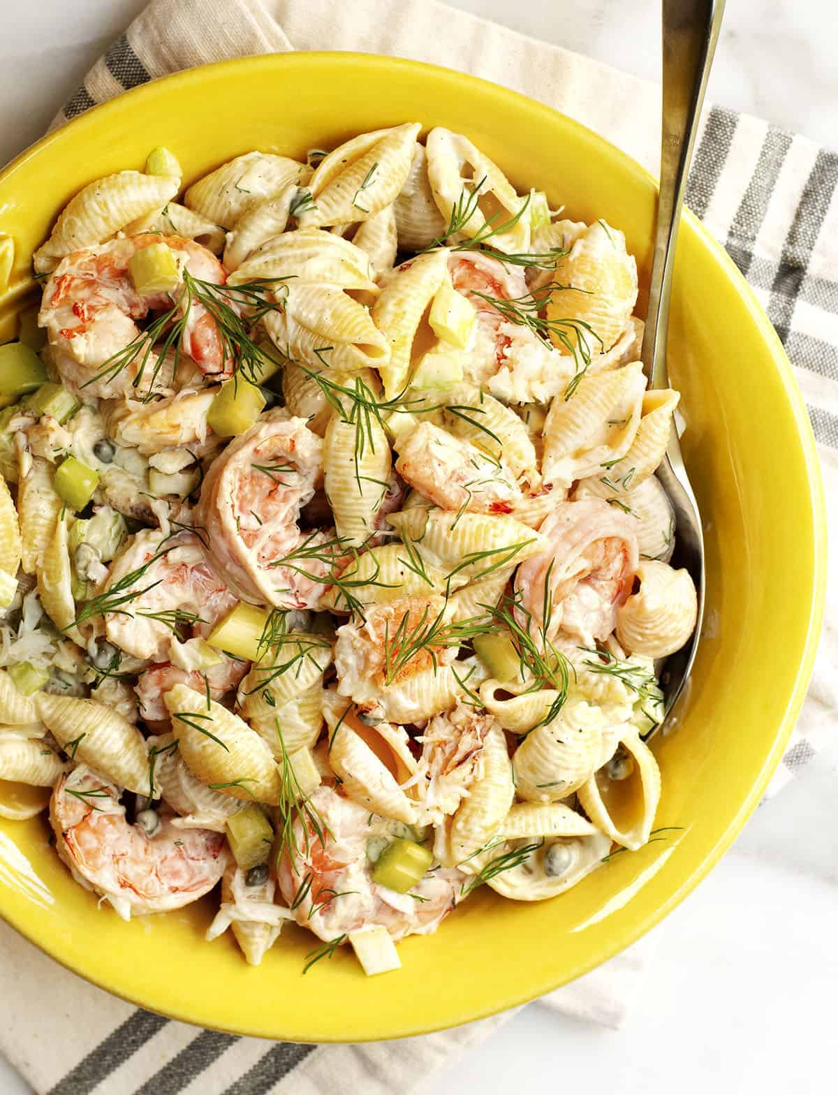 seafood pasta salad served in a yellow ceramic bowl photgraphed from above