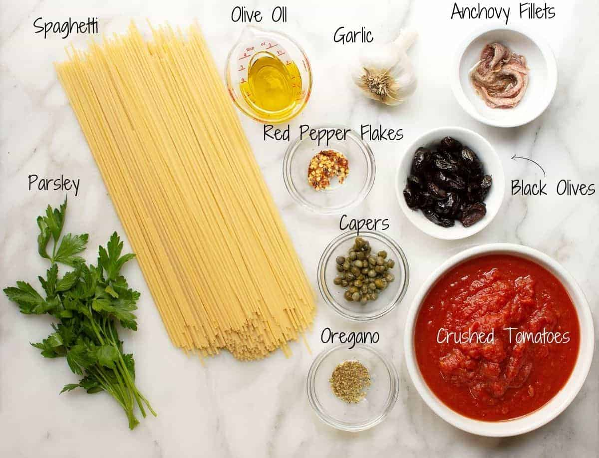 Spaghetti alla Puttanesca Ingredients on a white marble board