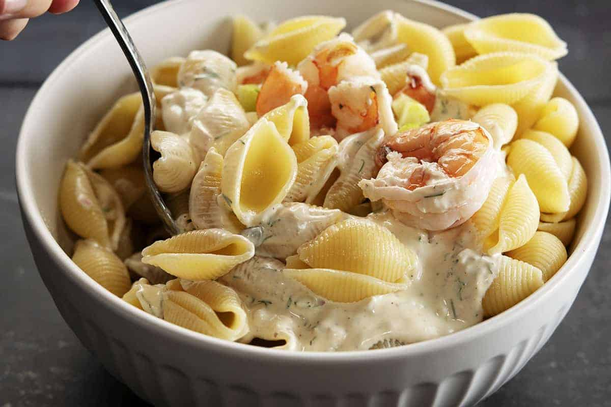 stirring seafood pasta salad ingredients
