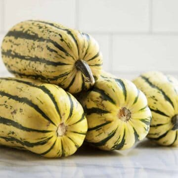 Delicata Squashes stacked on a marble board