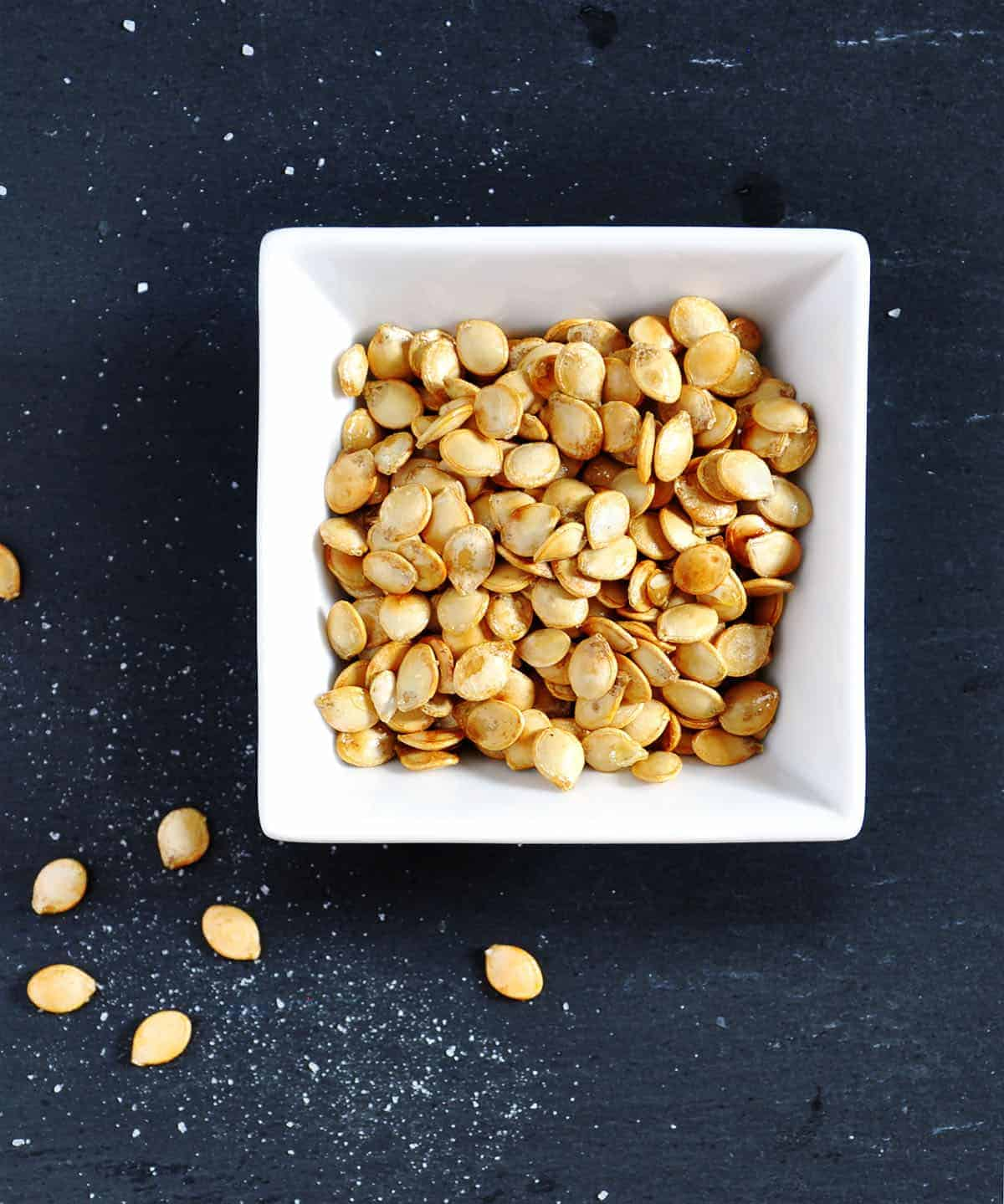roasted delicata squash seeds in a square white bowl