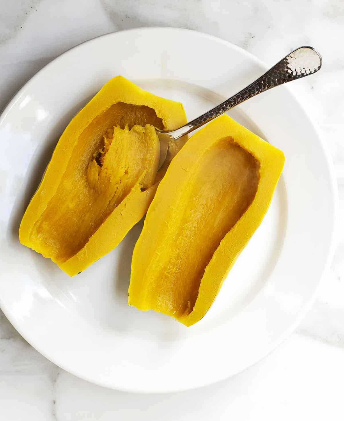 Scooping out roasted delicata squash on a white plate