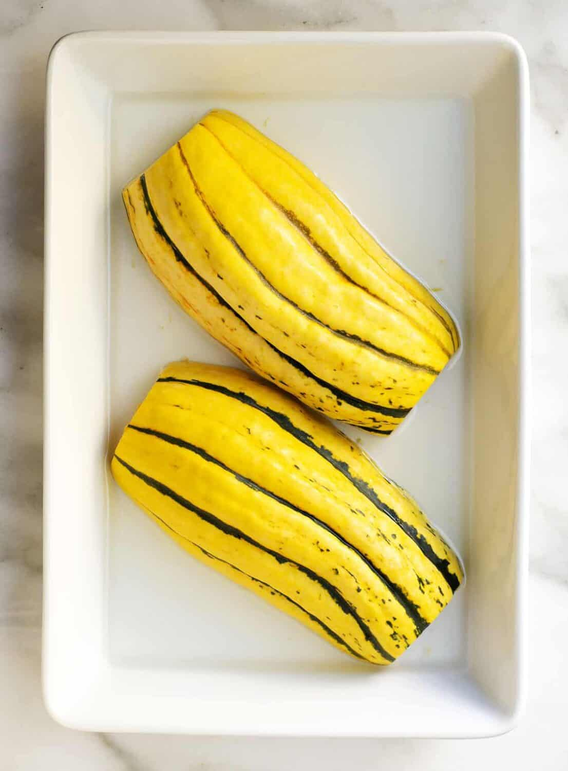 raw delicata squash in water in a baking dish