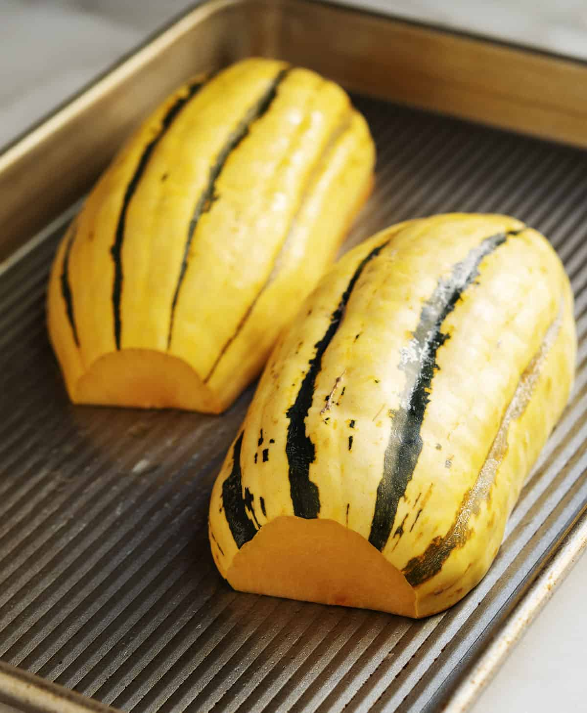 raw delicata squash on baking sheet