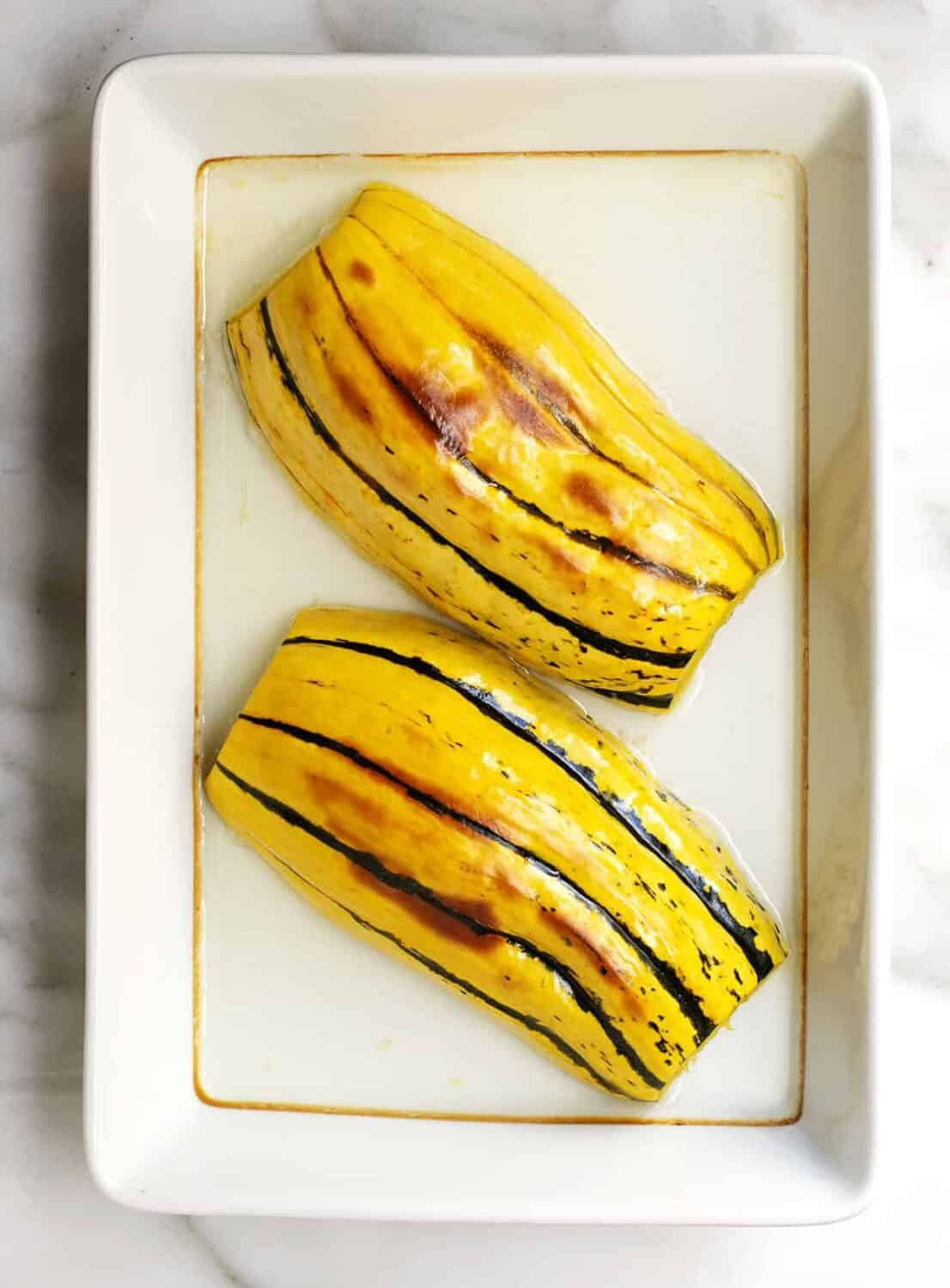 roasted delicata squash in water in a baking dish