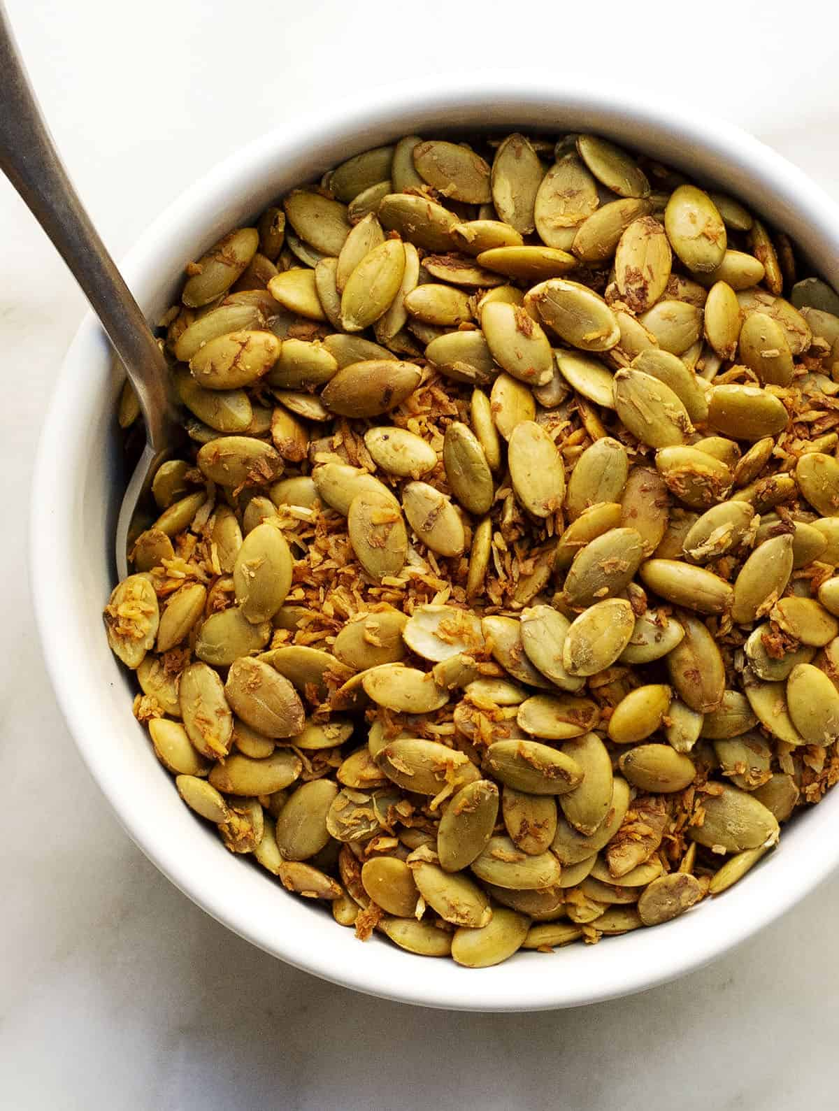 Toasted Coconut and Pumpkin Seeds in a white bowl