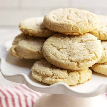 Almond Flour Sugar Cookies stacked on a white cake plate