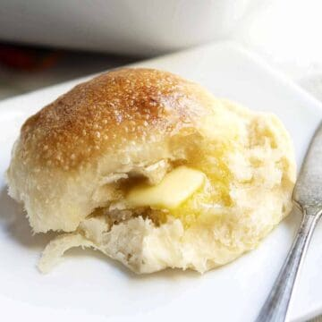Brioche Roll served on a white plate with butter