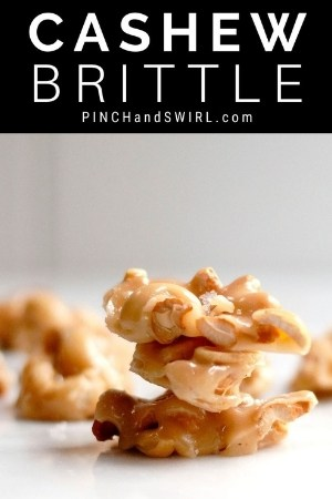 cashew brittle stacked on a white marble board
